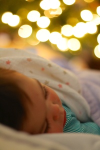 Sick baby Mattelyn asleep with her rosy chapped cheeks next to the Chrismas Tree.