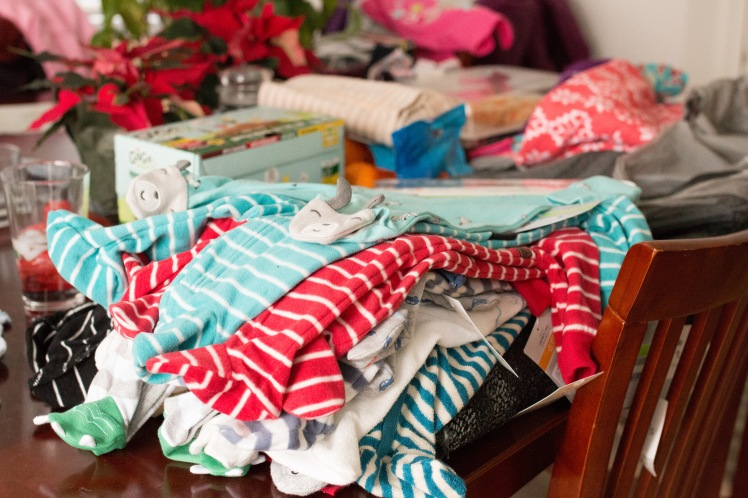 Newborn clothes to wash staged on the kitchen table...